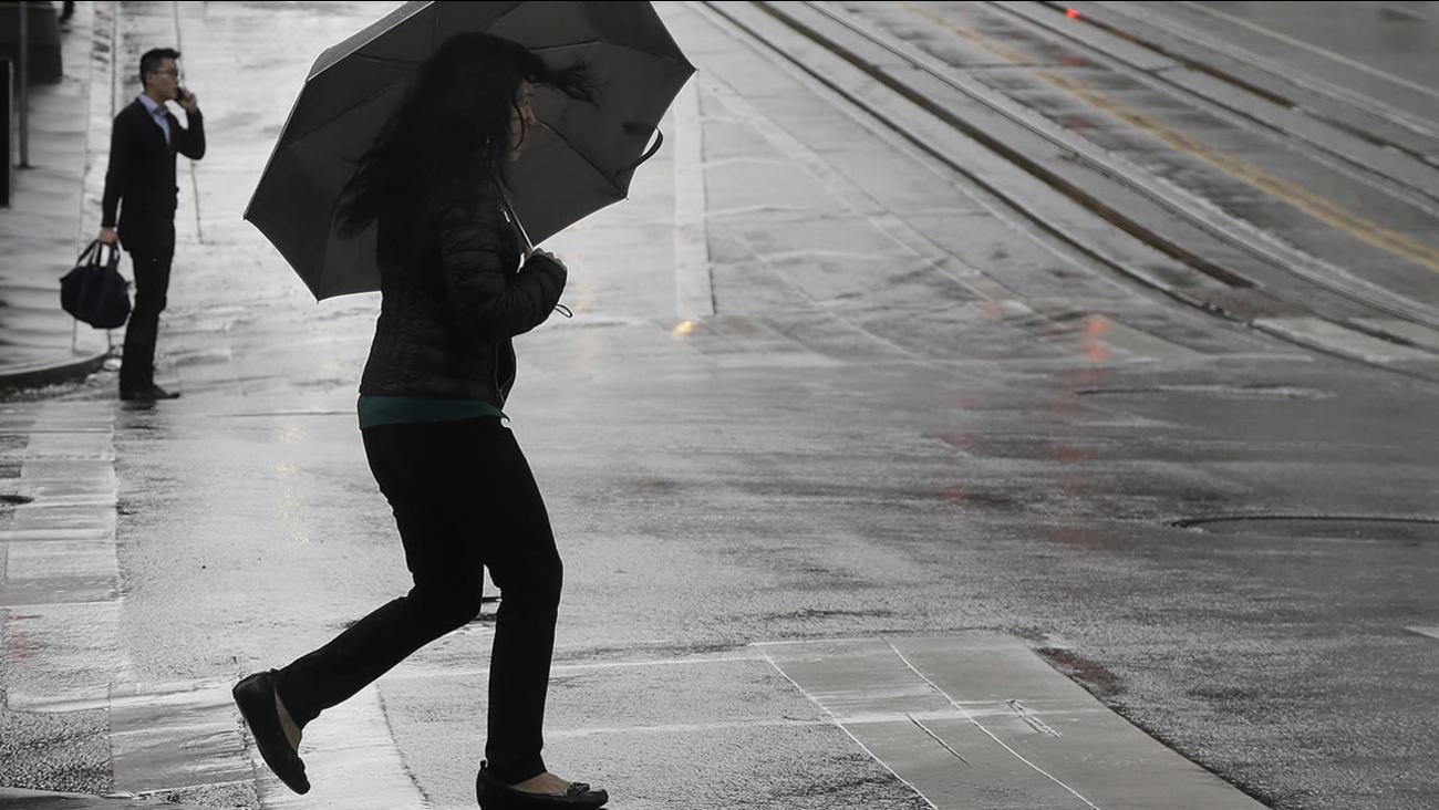 A woman carries an umbrella as she crosses California Street in San Francisco, Tuesday, Dec. 22, 2015. (AP Photo/Jeff Chiu)