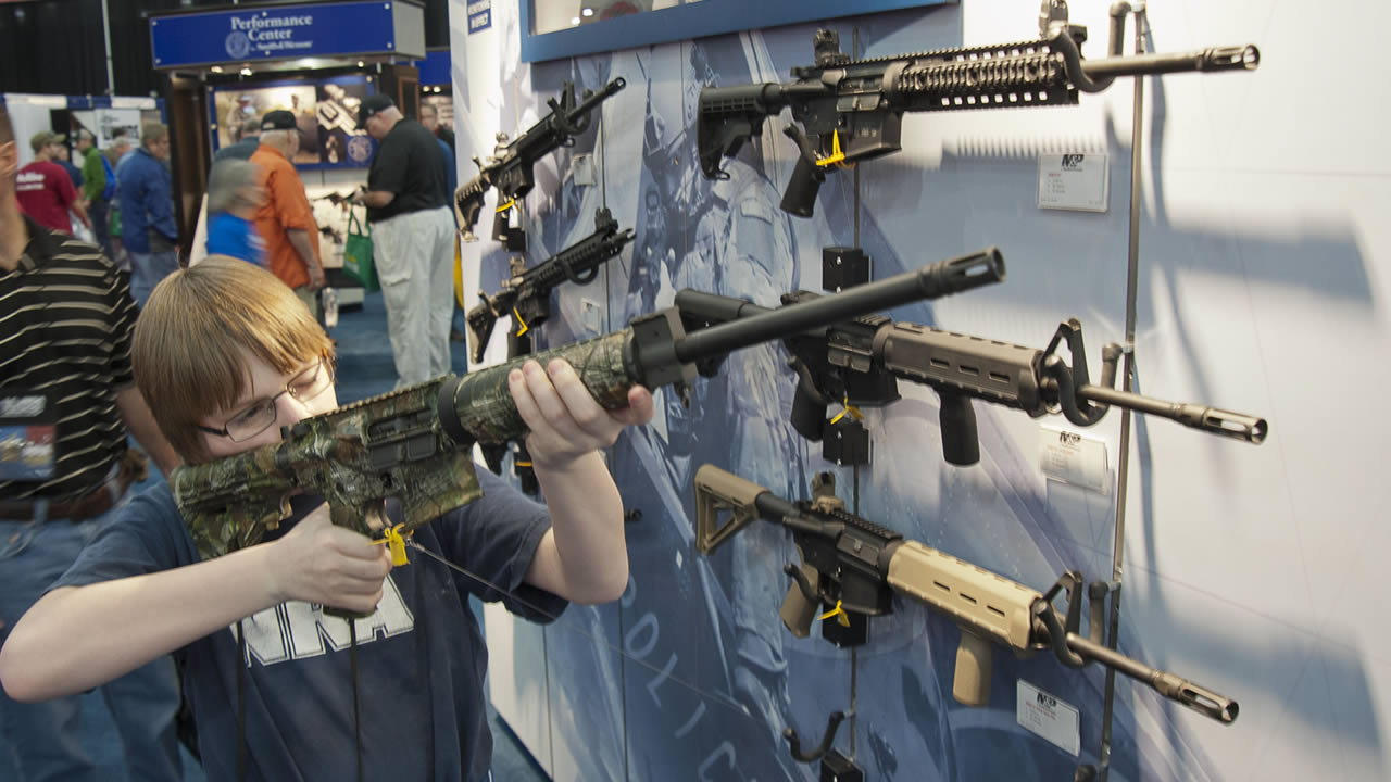A young man who chose not to give his name sizes-up an assault style rifle during the National Rifle Association's annual convention on May 3, 2013 in Houston. (AP Photo/Steve Ueckert)