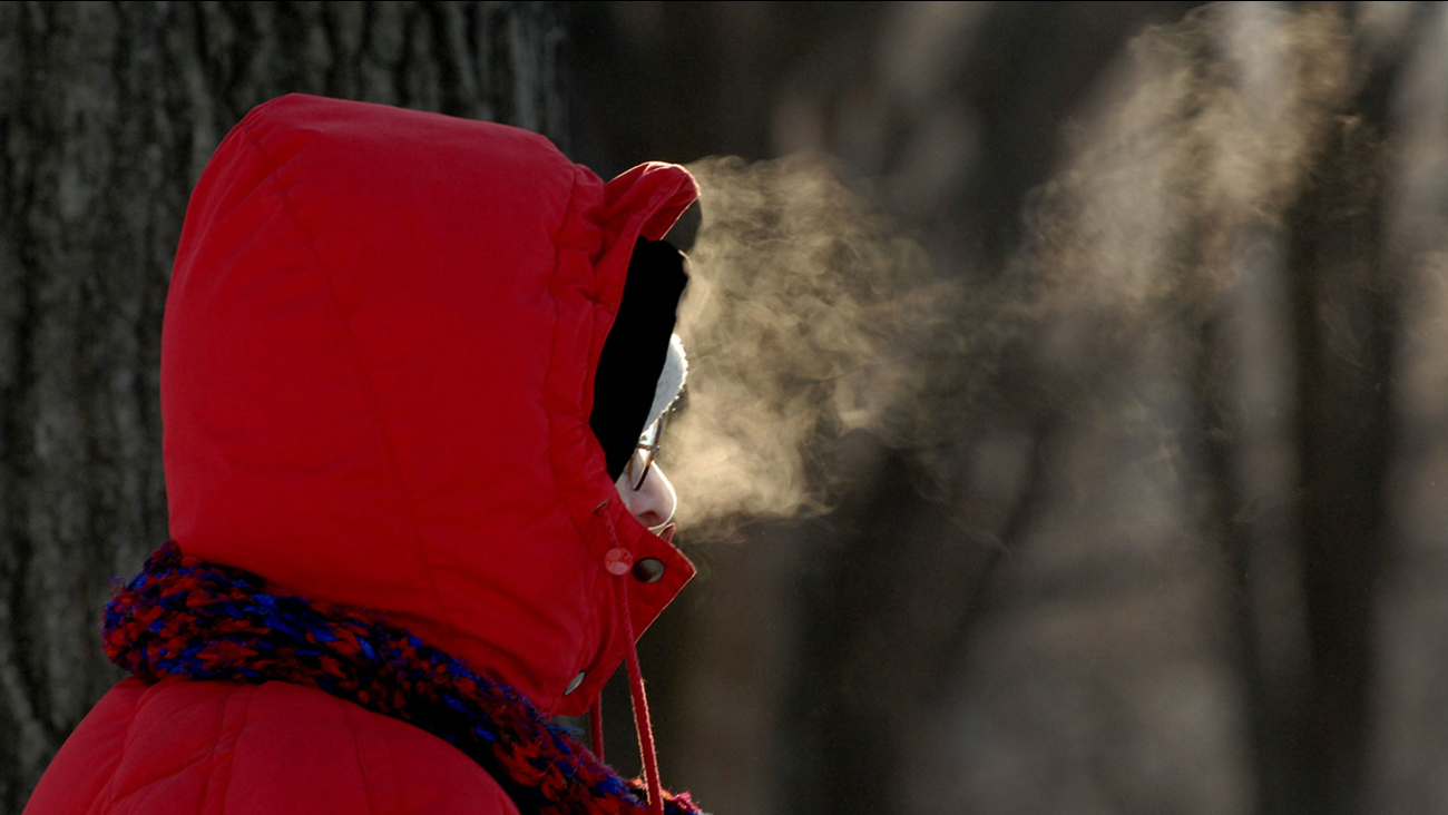 The breath of a bundled-up pedestrian is silhouetted on a frigid day