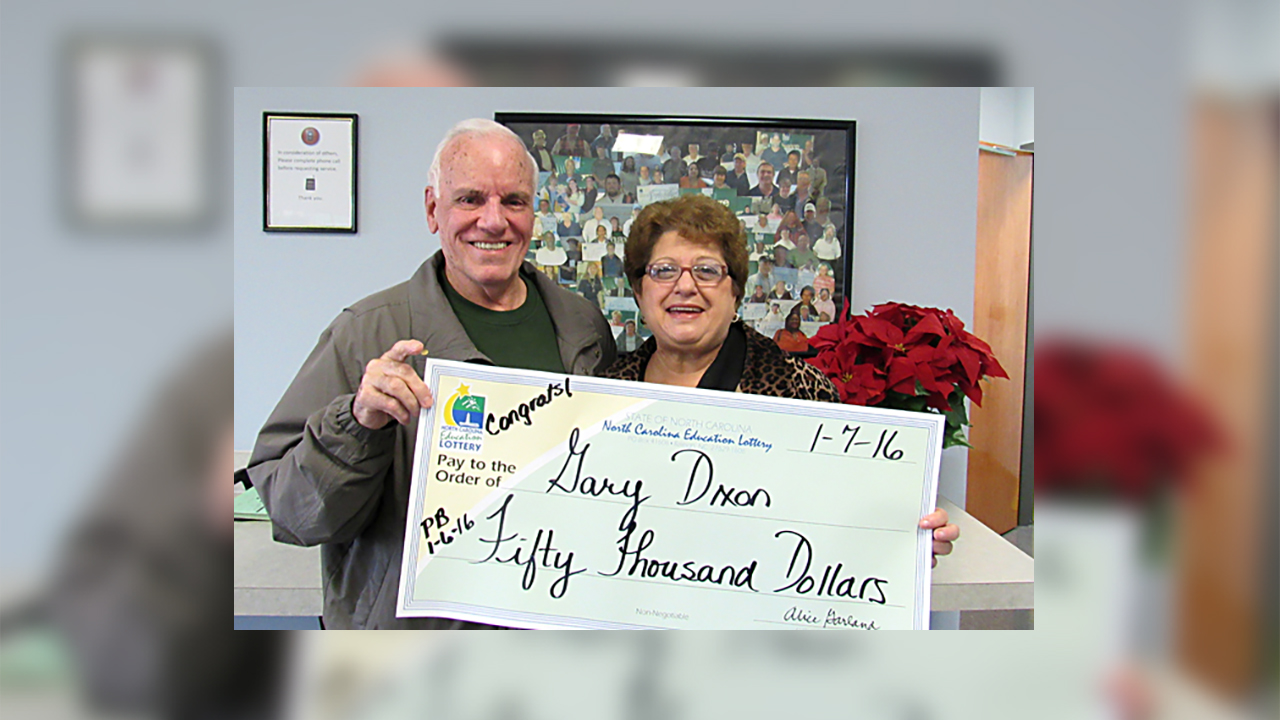 Gary Dixon and his wife with their Powerball winnings on Thursday.