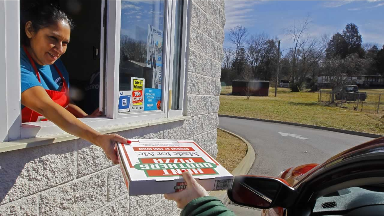 In this Feb. 6, 2015 photo, Maria Witkowski hands a Hunt Brothers Pizza from the drive-thru window to a customer at the Rightway Foodmart in Andersonville, Tenn.