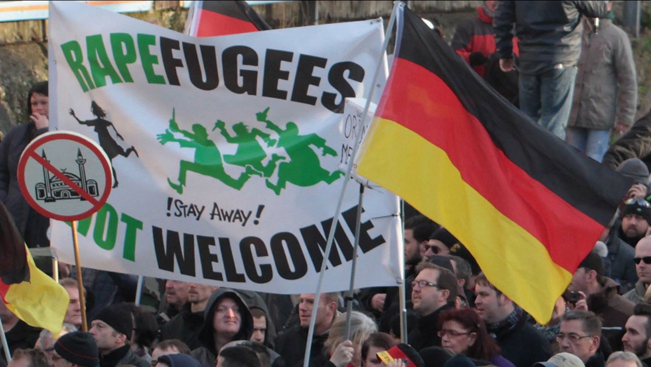 """Right-wing demonstrators hold a sign """"Rapefugees not welcome - !Stay away!"""""""