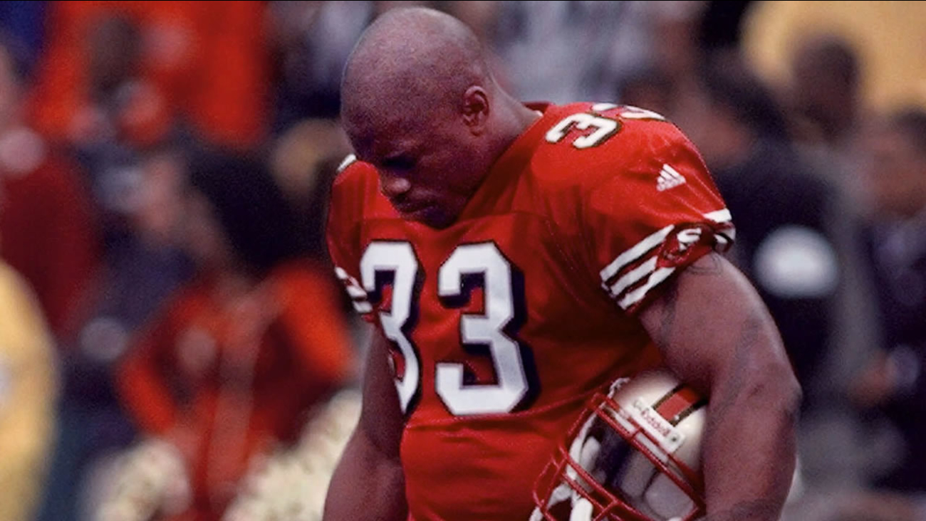 49ers running back Lawrence Phillips bows his head in a moment of silence for Walter Payton before a game against the Steelers on Nov. 7, 1999, in San Francisco. (AP Photo/Paul Sakuma)