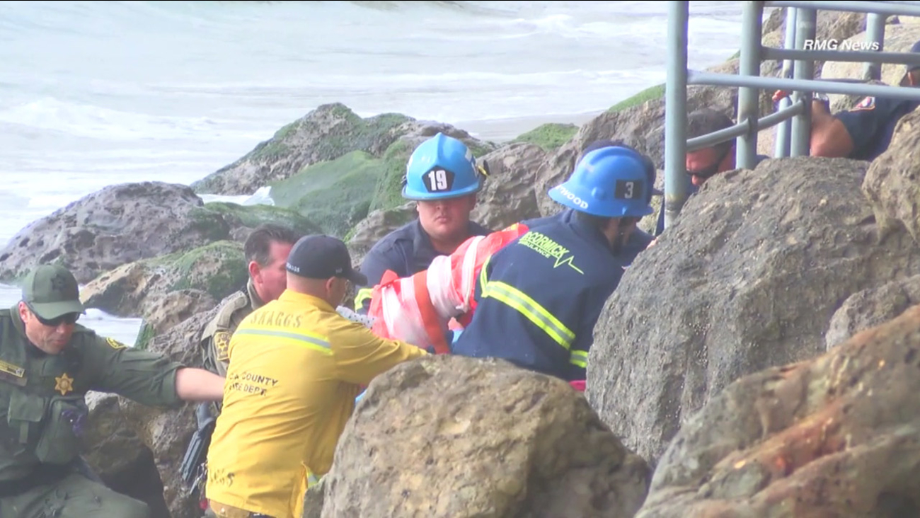 Rescue personnel lifted a woman from the rocks along a Malibu beach after she fell from a balcony on Saturday, Jan. 16, 2016.