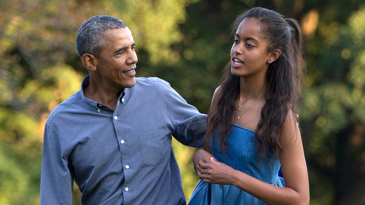 In this Aug. 23, 2015 file photo, President Barack Obama and his daughter Malia walk across the South Lawn of the White House in Washington.