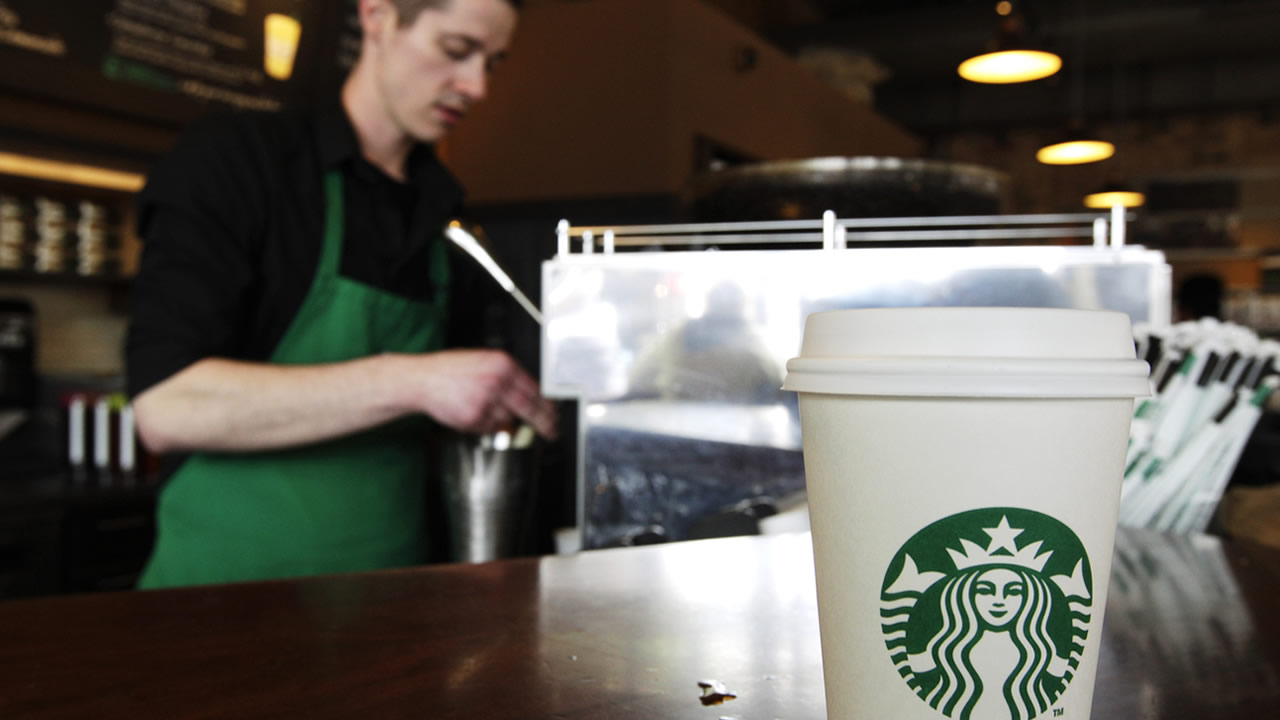 In this Friday, April 27, 2012, photo, a Starbucks drink waits for a customer to pick it up as barista Josh Barrow prepares another, in Seattle. (AP Photo/Ted S. Warren, File)
