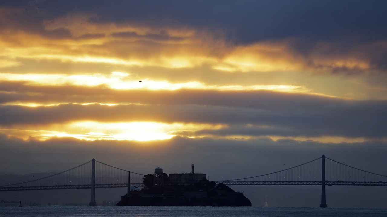 The sun rises behind Alcatraz Island and the San Francisco-Oakland Bay Bridge Thursday, Jan. 7, 2016, in this view Sausalito, Calif., after a couple days of storms.