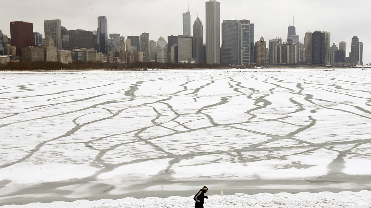 A lone jogger runs in the snow near the Adler Planetarium and Monroe Harbor on Lake Michigan Friday, Jan. 22, 2016, in Chicago.