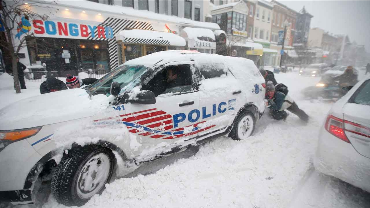 People pitch in to get a DC Metro police car moving again on 18th Street NW, Saturday, Jan. 23, 2016 in Washington.