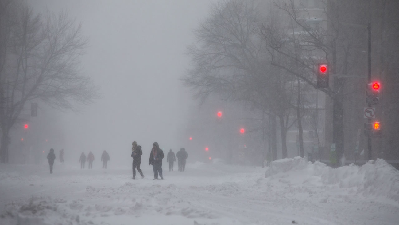 People walk on snow-covered streets in downtown Washington on Saturday, Jan. 23, 2016.