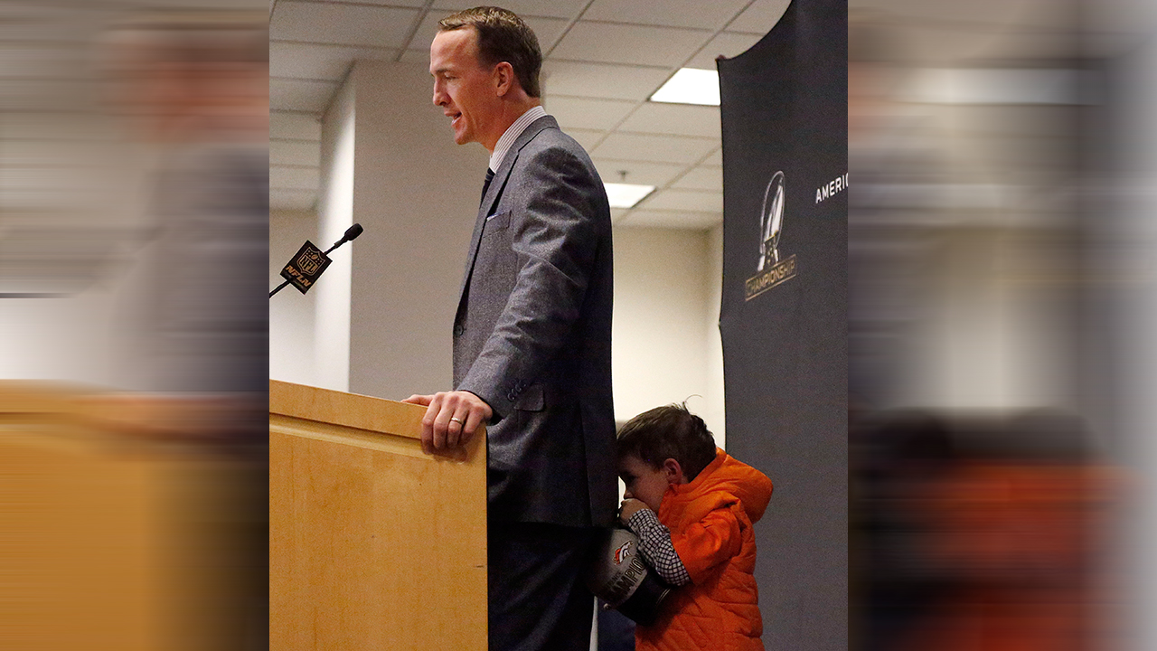 Denver Broncos quarterback Peyton Manning's son, Marshall, hides behind his father