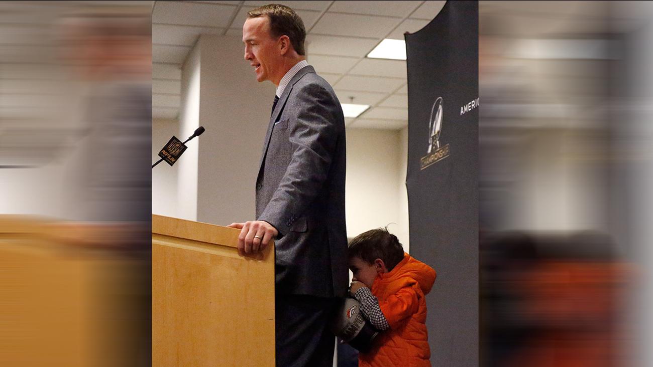 Denver Broncos quarterback Peyton Manning's son, Marshall, hides behind his father