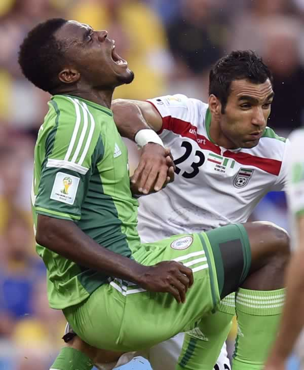 "<div class=""meta image-caption""><div class=""origin-logo origin-image ""><span></span></div><span class=""caption-text"">Nigeria's Emmanuel Emenike, left, grimaces after a challenge from Iran's Mehrdad Pouladi during the group F World Cup soccer match between Iran and Nigeria. (AP Photo/Martin Meissner)</span></div>"