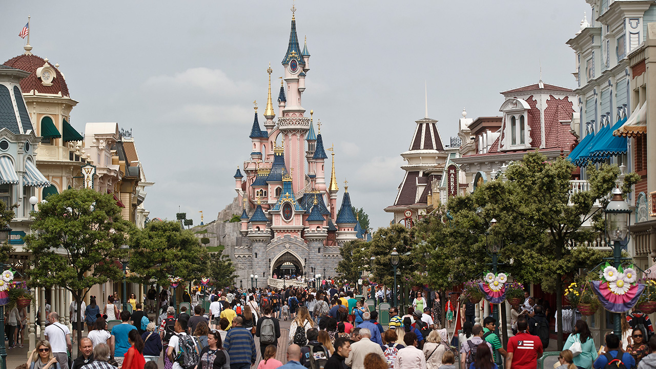 In this undated file photo, visitors walk toward the Sleeping Beauty's Castle, background, at Disneyland Paris in Chessy, France, east of Paris.
