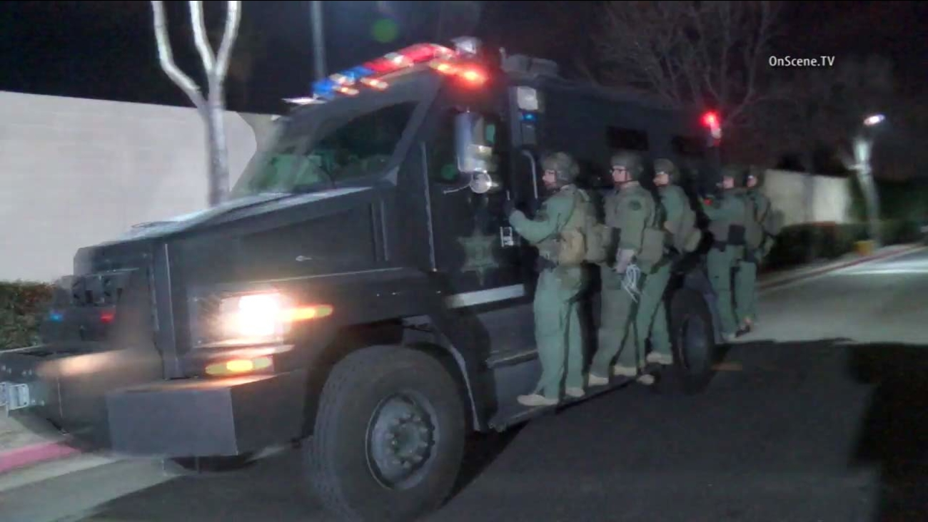 An Orange County SWAT unit rides on an armored vehicle during a raid on Thursday, Jan. 28, 2016.