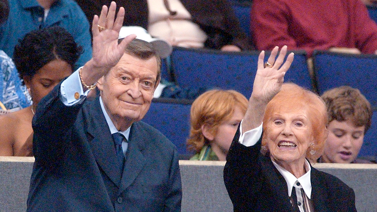 Los Angeles Lakers announcer Chick Hearn and wife, Marge, wave to fans attending the Lakers' game against the Portland Trail Blazers on Friday night, March 29, 2002.