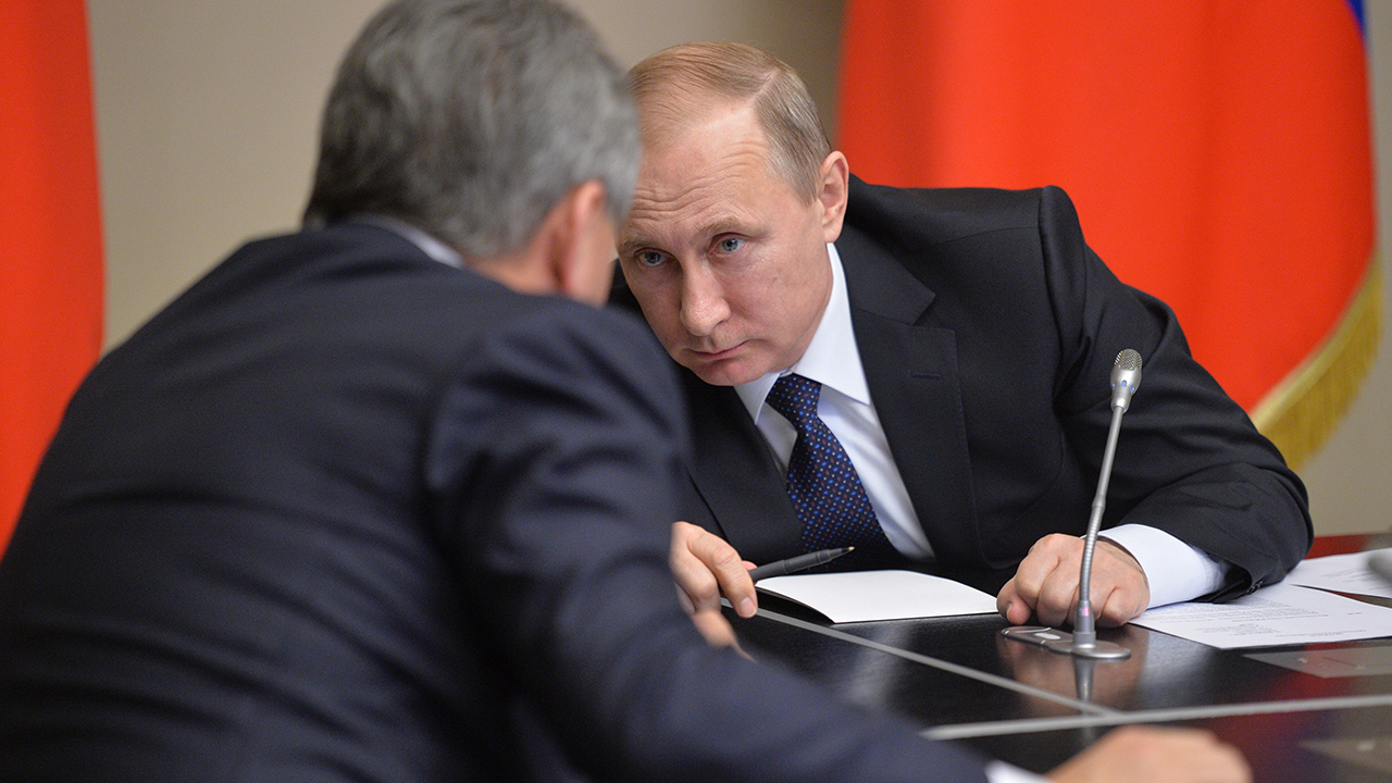 Russian President Vladimir Putin, right, and Defense Minister Sergei Shoigu attend a conference call with Russian military commanders involved in war games in southwestern Russia, in the Novo-Ogaryovo residence outside Moscow, Russia, Thursday, Feb. 11