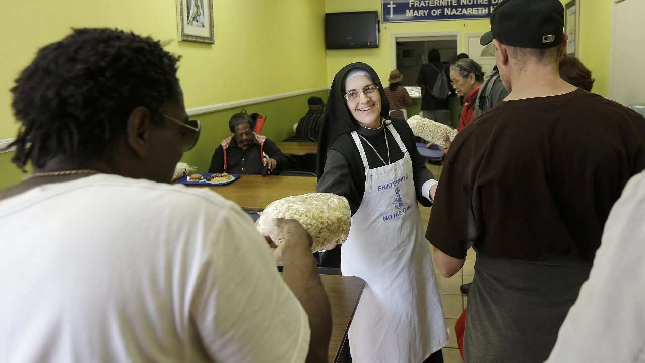 FILE - In a Tuesday, Feb. 9, 2016 file photo, Sister Mary Valerie, center, hands out bags of popcorn at the Fraternite Notre Dame Mary of Nazareth Soup Kitchen in San Francisco.