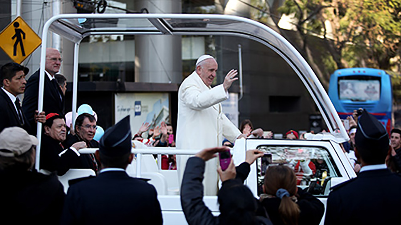 Pope Francis waves to the people from the popemobile along his route to the National Palace in Mexico City, Saturday, Feb. 13, 2016.