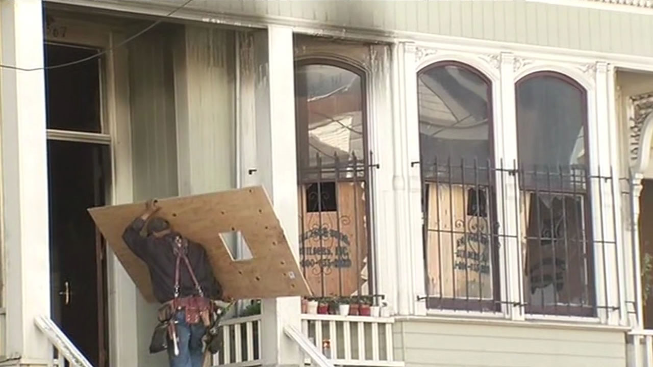 A worker boards up windows in a San Francisco home after it caught fire Feb. 13, 2016.