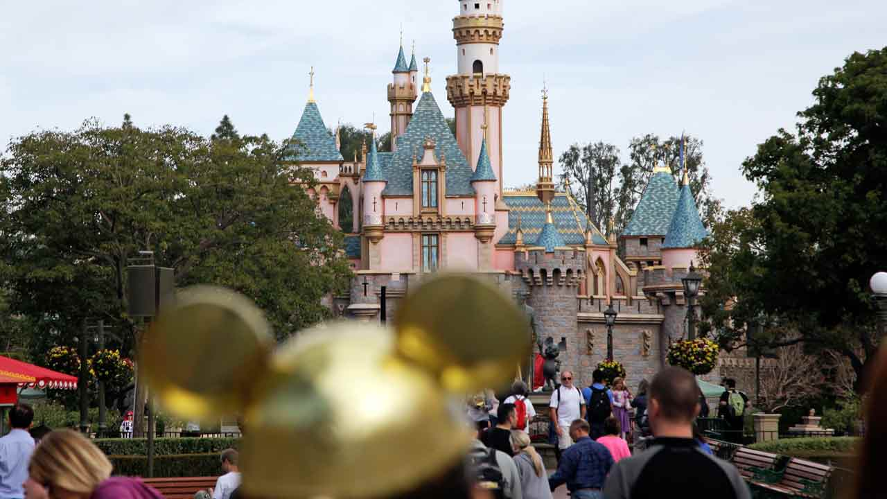 FILE - In this Jan. 22, 2015 file photo, visitors walk toward the Sleeping Beauty's Castle in the background at Disneyland Resprt in Anaheim, Calif.