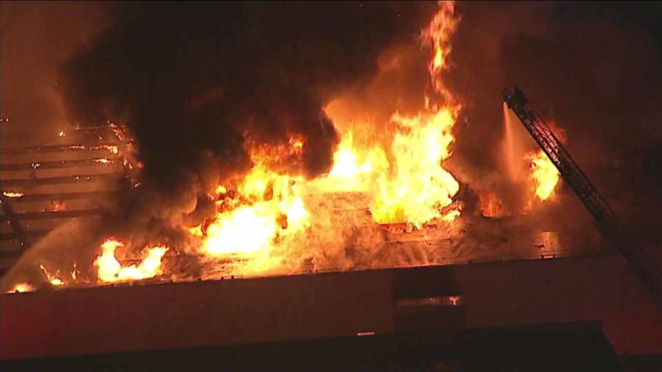 Firefighters battle a defensive blaze at a commercial building in Rancho Dominguez, Calif. on Monday, Feb. 22, 2016.