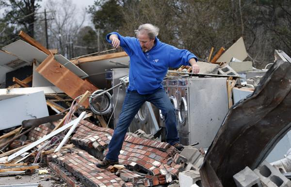 "<div class=""meta image-caption""><div class=""origin-logo origin-image ap""><span>AP</span></div><span class=""caption-text"">Laundromat manager Brad Poindexter, of Danville, Va., jumps over bricks at his damaged business after a deadly storm that swept through Waverly, Va., Wednesday, Feb. 24, 2016 (Steve Helber)</span></div>"