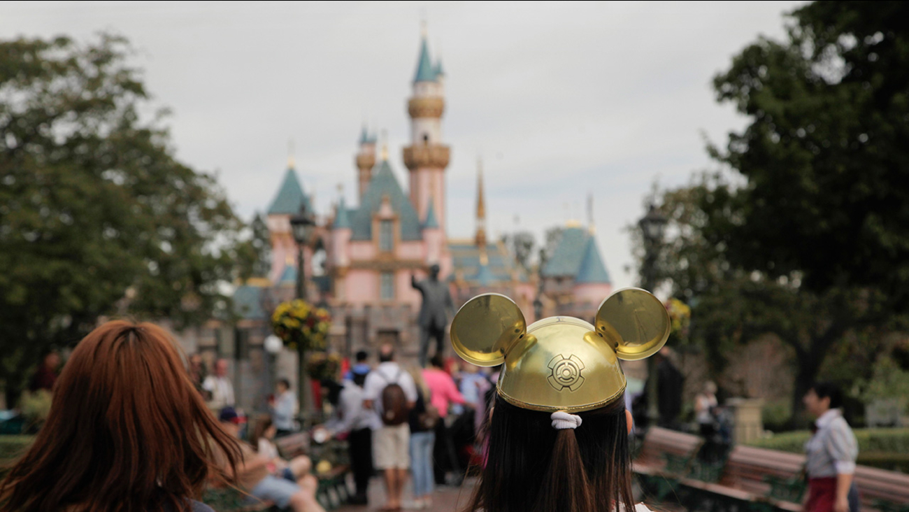 FILE - In this Jan. 22, 2015, file photo, a woman with a Mickey Mouse hat walks toward Sleeping Beauty's Castle at Disneyland, in Anaheim, Calif.