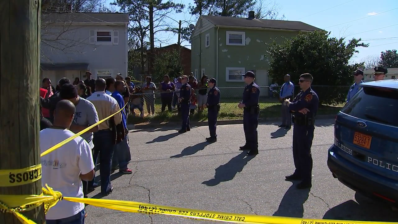 Police officers face a crowd across crime scene tape after an officer-involved shooting in southeast Raleigh.