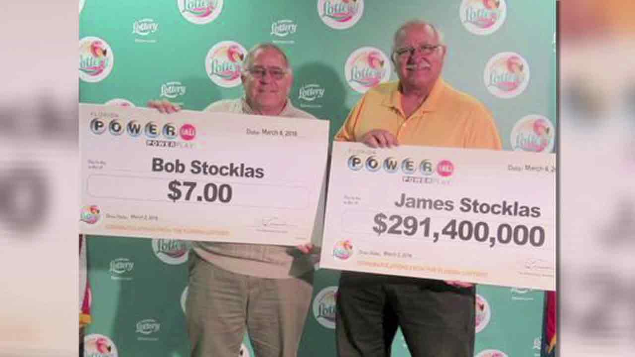 Two brothers hold their checks after winning very different prizes in a Florida lottery on Wednesday, March 2, 2016.