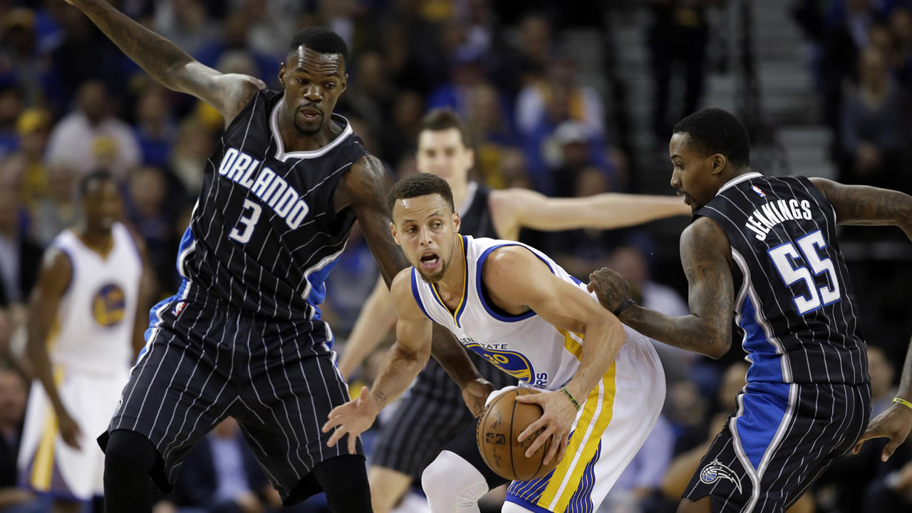 Warriors' Stephen Curry is defended by Magic's Dewayne Dedmon during an NBA basketball game Monday, March 7, 2016, in Oakland, Calif. (AP Photo/Marcio Jose Sanchez)