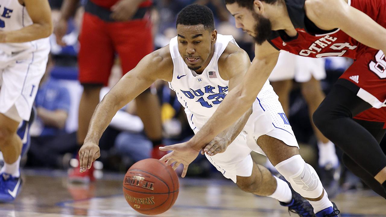 Duke guard Matt Jones (13) and North Carolina State guard Caleb Martin (14) scramble for a loose ball Wednesday at the ACC Tournament.