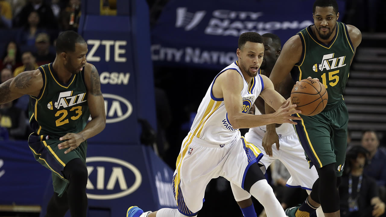 Warriors' Curry drives the ball between Jazz's Johnson and Favors during the first half of an NBA basketball game on March, 9, 2016 in Oakland, Calif. (AP Photo)
