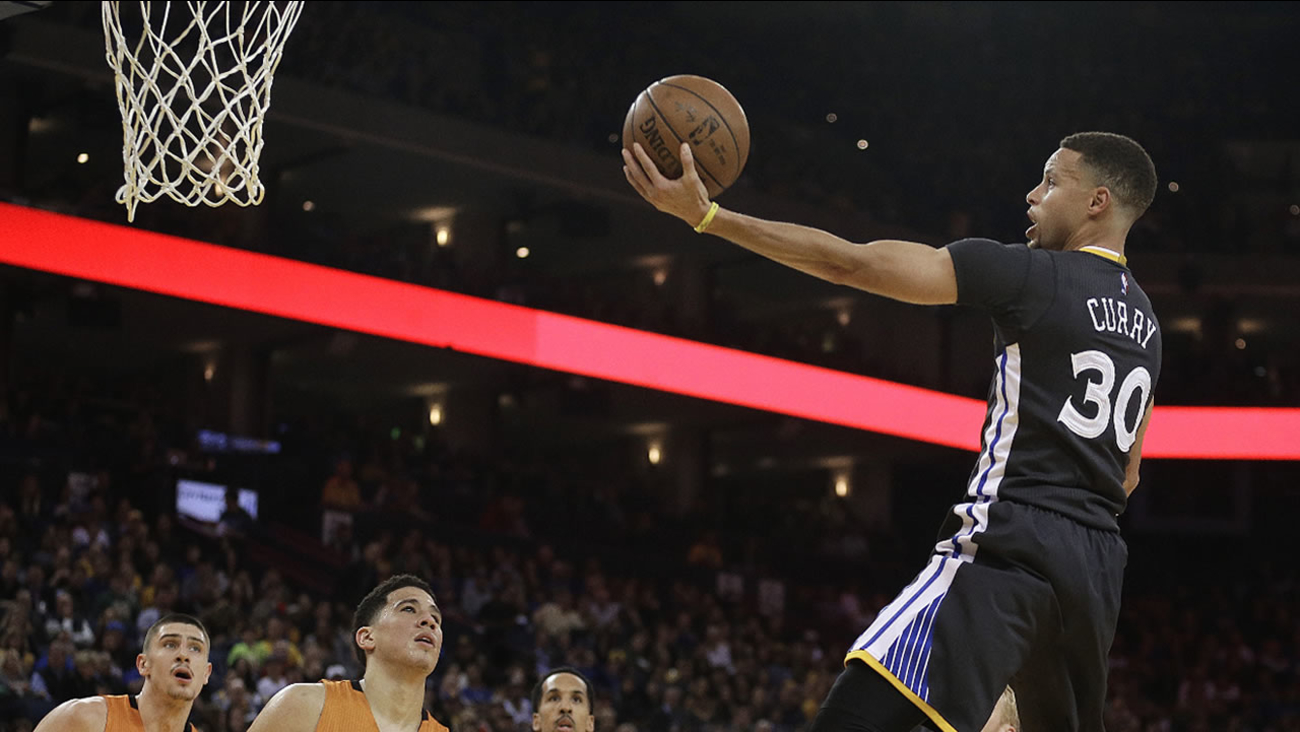 Golden State Warriors' Stephen Curry lays up a shot against the Phoenix Suns during the first half of their game on Saturday, March 12, 2016, in Oakland, Calif.