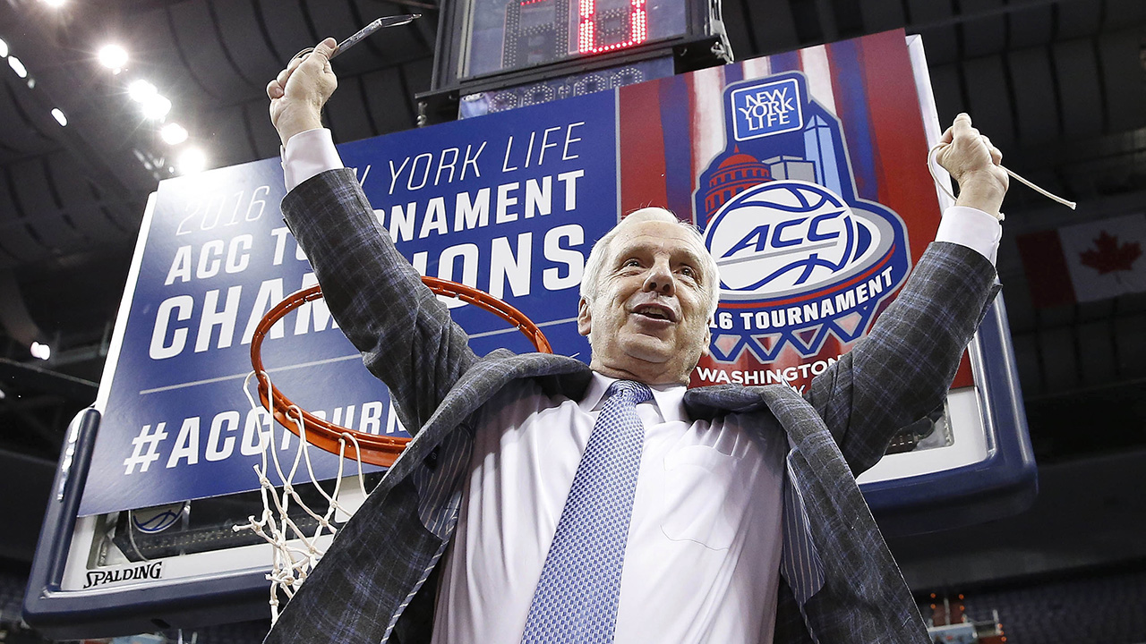 North Carolina head coach Roy Williams holds part of the net after an NCAA college basketball game in the championship of the Atlantic Coast Conference tournament against Virginia