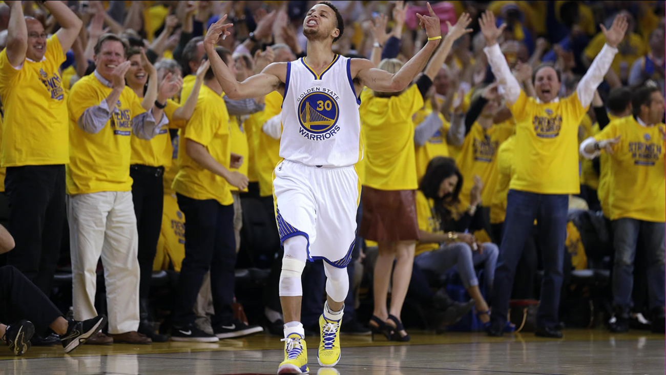 In this May 13, 2015, file photo, fans cheer as Warriors' Curry reacts after scoring during Game 5 in the NBA playoff basketball series against the Grizzlies. (AP Photo/Ben Margot)