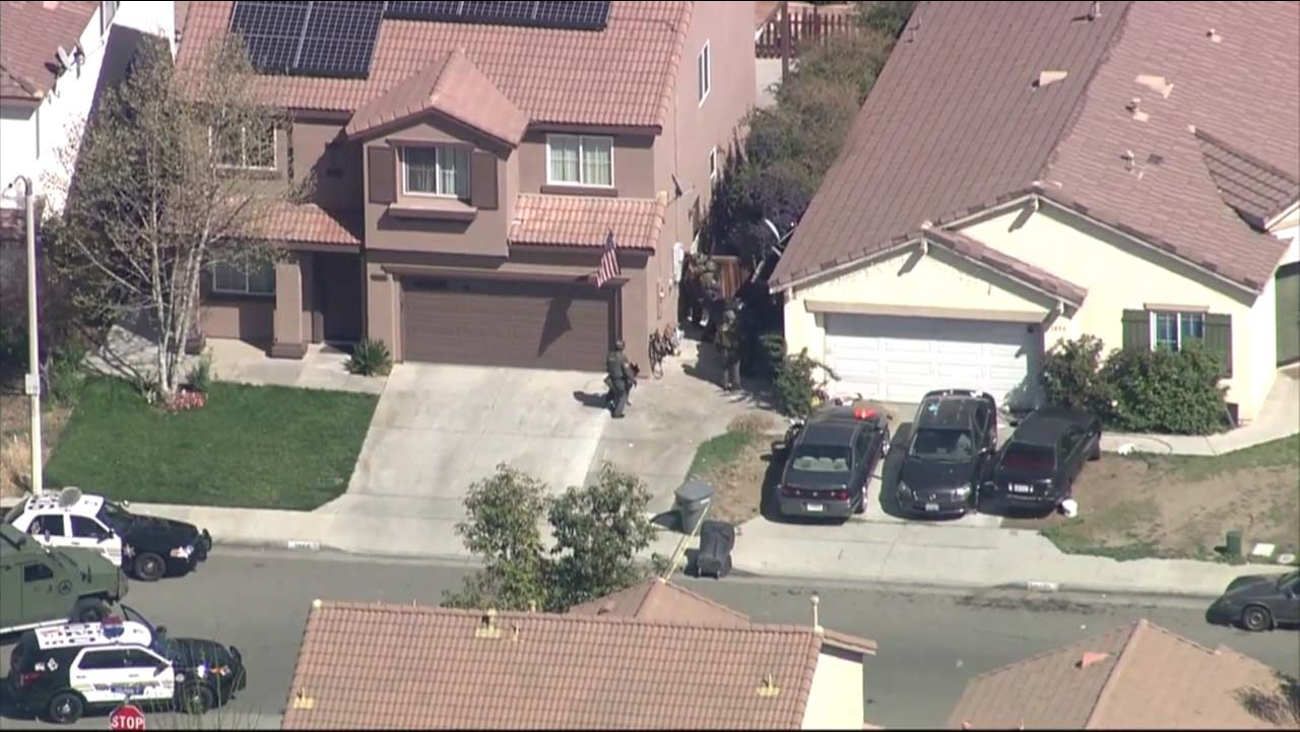 Riverside sheriff's deputies search a residential neighborhood near Dolphin Drive and Mildred Street in Perris for a robbery suspect.