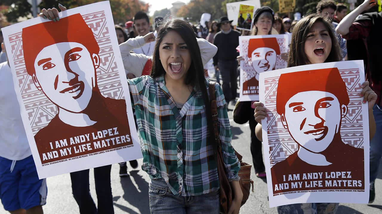 In this Oct. 29, 2013, file photo, protesters hold an image of shooting victim Andy Lopez, during a march in Santa Rosa, Calif.  (AP Photo/Marcio Jose Sanchez, file)