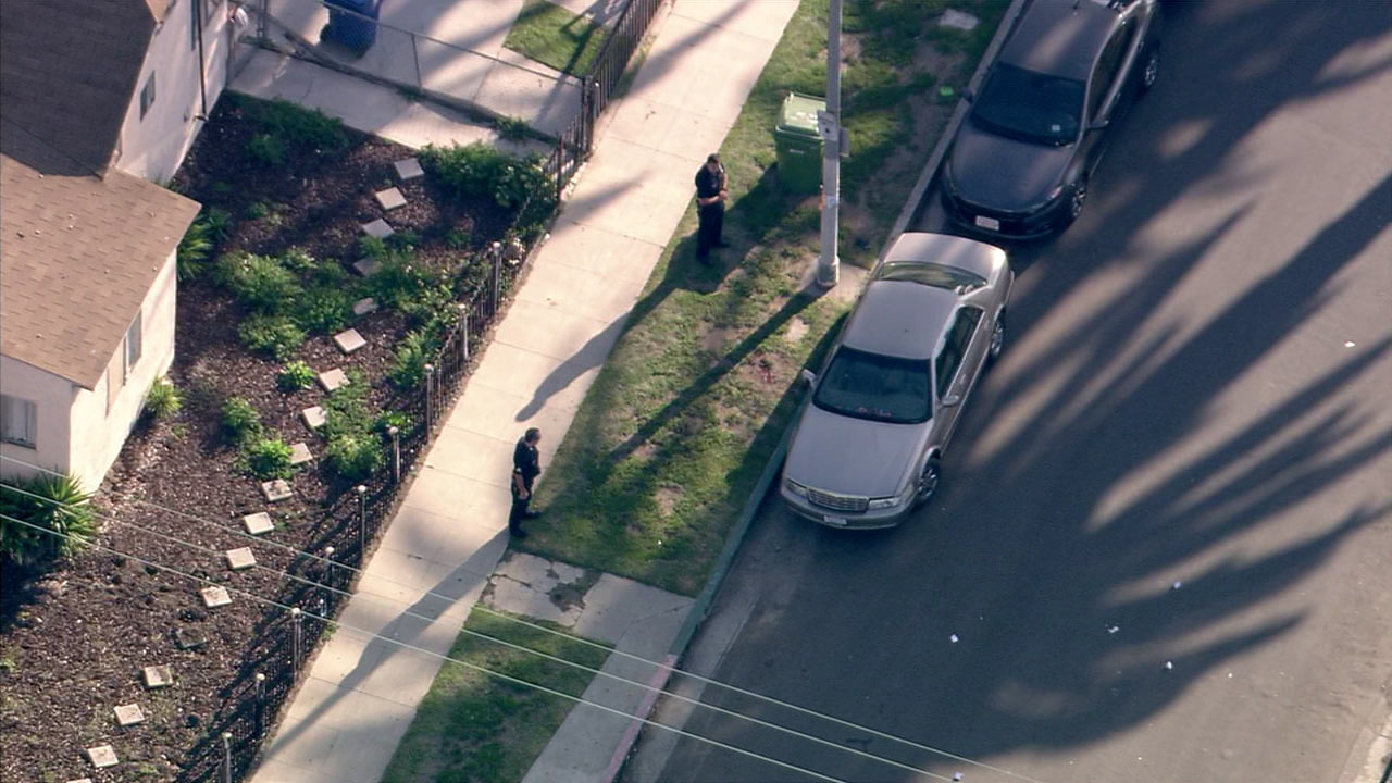 Law enforcement officials investigate the scene where a man was shot in a car in South Los Angeles on Thursday, March 17, 2016.