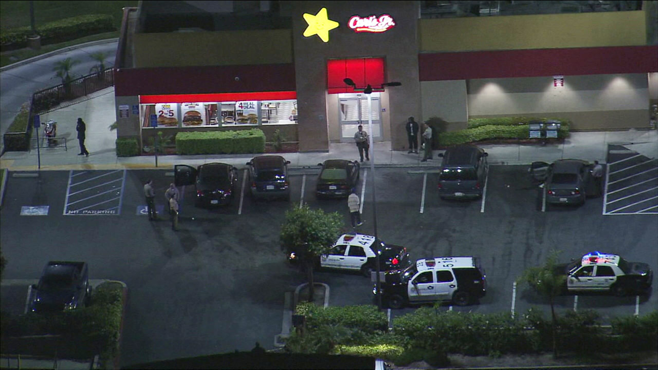 Law enforcement officials investigate the scene of a shooting at a Carl's Jr. restaurant in Compton on Thursday, March 18, 2017.