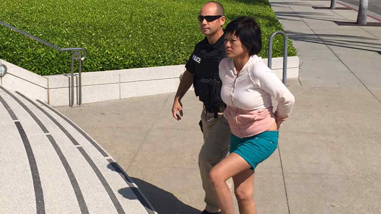 Trang Pham, 46, being taken into custody in Santa Ana, Calif. on Friday, March 18, 2016, for allegedly stealing Buddha statues from a temple.