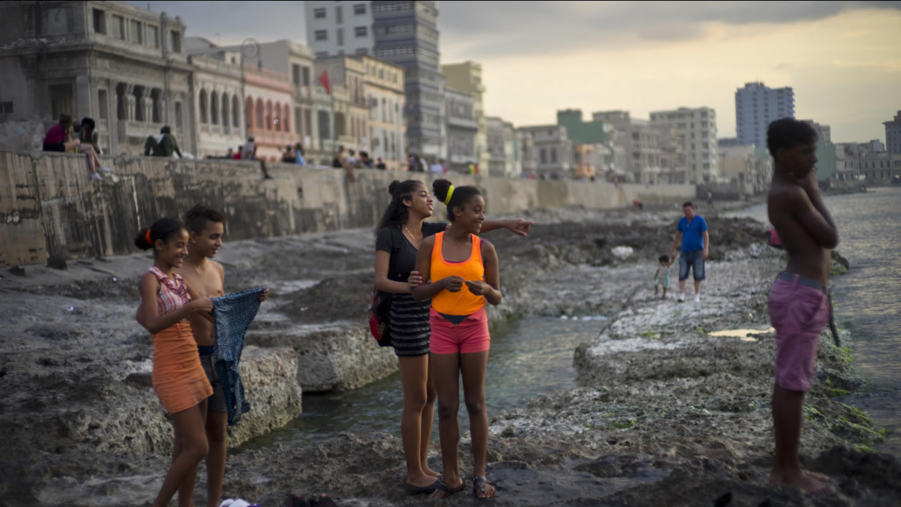 Youths spend the afternoon at Havana's Malecon, in Cuba, Friday, March 18, 2016. U.S. President Barack Obama will travel to the communist island March 20.