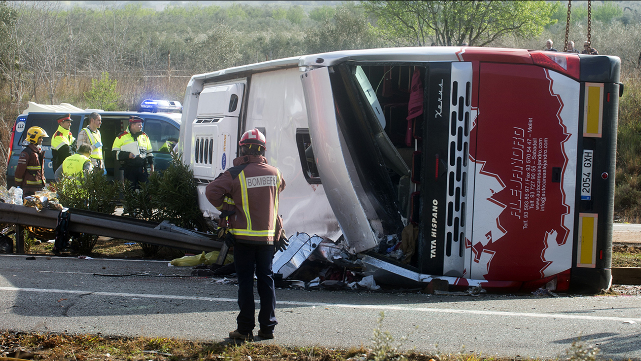 Emergency services personnel stand at the scene of a bus accident crashed on the AP7 highway that links Spain with France along the Mediterranean coast
