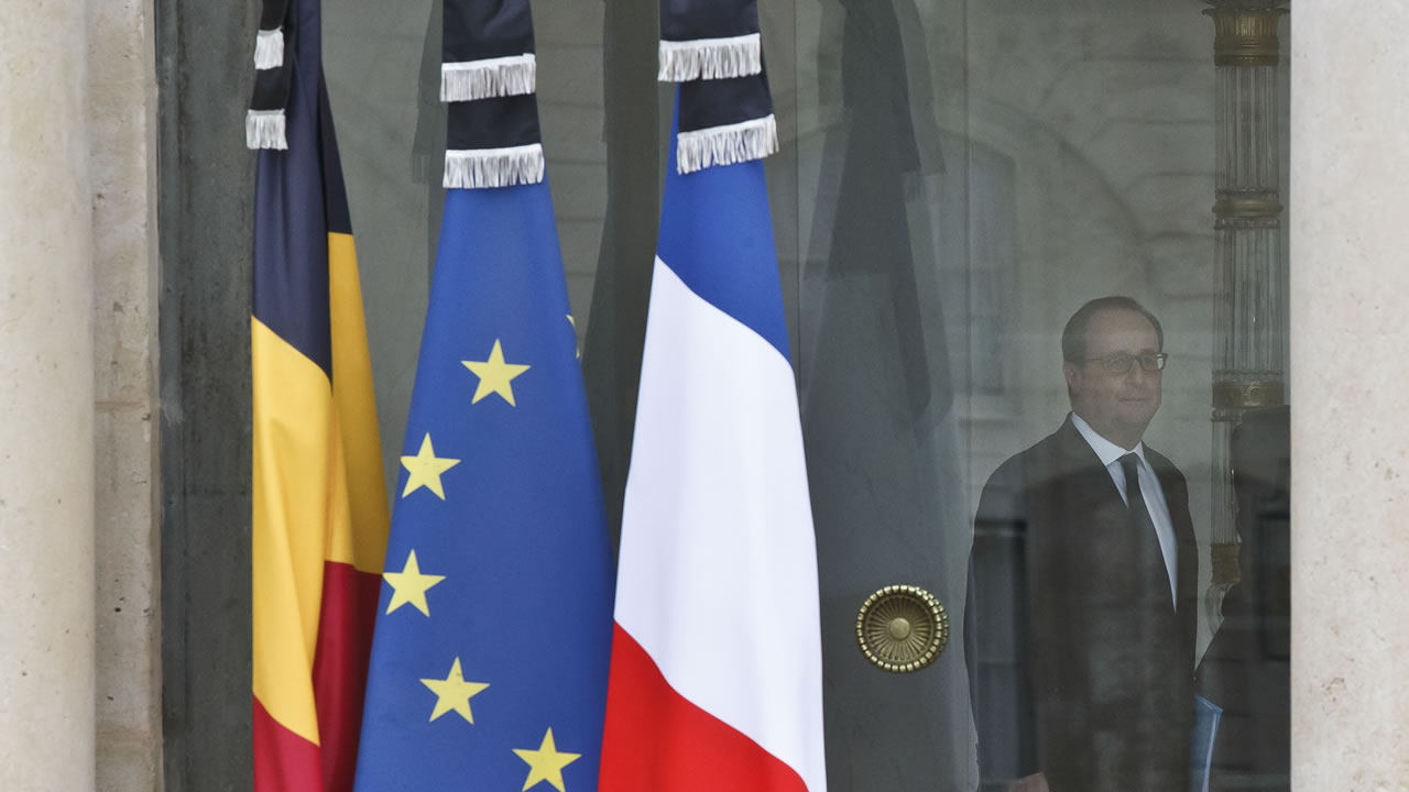 Black ribbons are affixed to the Belgian, left, European Union and French flags after the weekly cabinet meeting at the Elysee Palace in Paris, Thursday March 24, 2016.