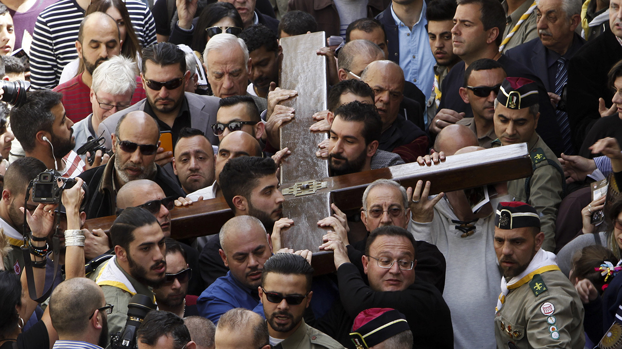 Christian faithful carry a cross during Good Friday in Jerusalem, Friday, March 25, 2016. Catholics and Protestants commemorated the crucifixion of Jesus Christ