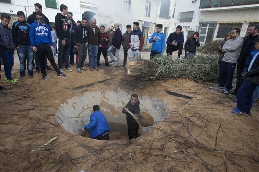 """<div class=""""meta image-caption""""><div class=""""origin-logo origin-image none""""><span>none</span></div><span class=""""caption-text"""">Youths shovel sand from a hole in the village square to erect a tree trunk in the shape of  cross in Tielmes, Spain. (AP Photo/Paul White) (AP)</span></div>"""