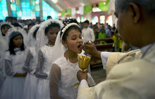 "<div class=""meta image-caption""><div class=""origin-logo origin-image none""><span>none</span></div><span class=""caption-text"">An Indian Catholic priest offers holy communion to Christian girls after Easter mass at a church in Gauhati, India. (AP Photo/Anupam Nath) (AP)</span></div>"
