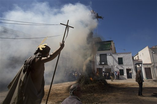 """<div class=""""meta image-caption""""><div class=""""origin-logo origin-image none""""><span>none</span></div><span class=""""caption-text"""">A religious figure is carried past a figure representing Judas burning on a cross in the village square in Tielmes, Spain, (AP Photo/Paul White) (AP)</span></div>"""