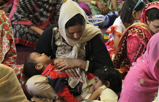 "<div class=""meta image-caption""><div class=""origin-logo origin-image none""><span>none</span></div><span class=""caption-text"">A Christian woman holds her children while she prays during an Easter service at St Anthony's Church in Lahore, Pakistan. (AP Photo/K.M. Chaudary) (AP)</span></div>"
