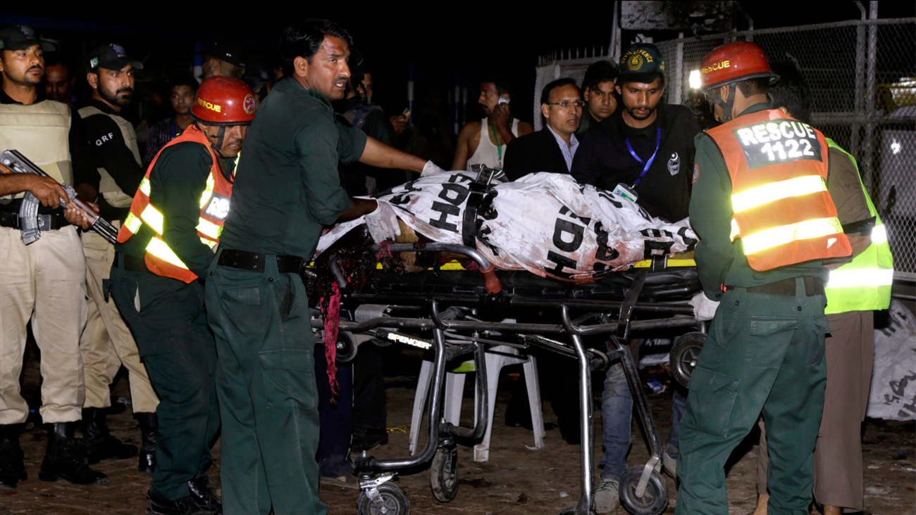 Pakistani rescue workers remove a dead body from the site of bomb explosion in a park in Lahore, Pakistan, Sunday, March, 27, 2016.